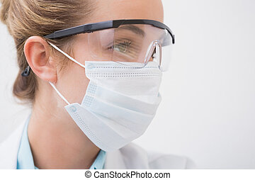 Dentist with surgical mask and protective glasses at the...