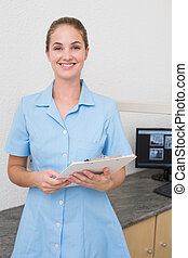 Smiling dental assistant looking at camera holding clipboard...