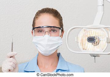 Dental assistant in mask holding dental explorer at the...