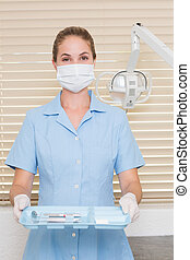 Dental assistant in mask holding tray of tools at the dental...