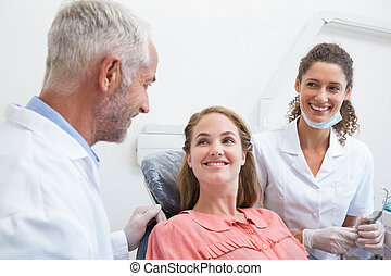 Dentist talking with patient while nurse prepares the tools...