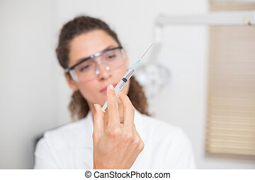 Dental assistant preparing an injection at the dental clinic
