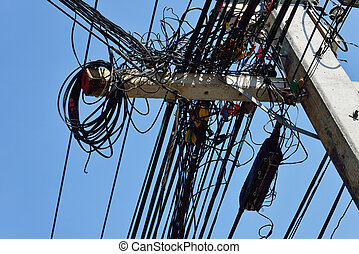 The chaos of cables and wires on electricity post