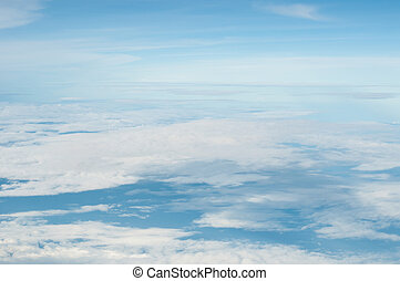fluffy white clouds and blue sky background seen from...