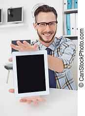 Happy casual businessman showing tablet pc in his office