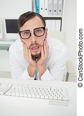 Nerdy nervous businessman working on computer  in his office