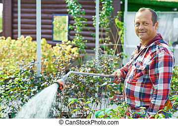 Gardener at work - Mature gardener looking at camera with...