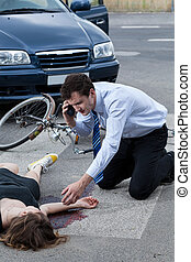 Man calling an ambulance for injured woman after road...