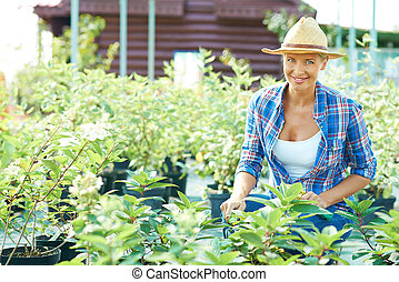 Gardening - Pretty female farmer looking at camera in the...