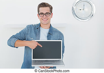 Nerdy businessman holding laptop smiling at camera in his...