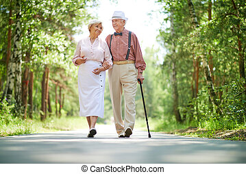 Summer walk - Happy seniors taking a walk in the park on...