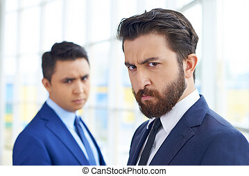 Businessman frowning - Frowning businessman looking at...