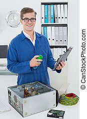 Smiling technician working on broken computer in his office