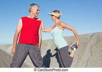 Active senior couple stretching before a jog on a sunny day