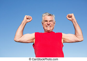 Active senior man cheering in red tank top on a sunny day