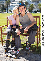 Active senior couple ready to go rollerblading on a sunny...