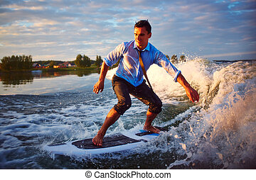 Adventurous sport - Active young man surfboarding at summer...