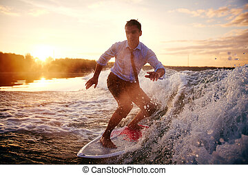 Water recreation - Young man in wet clothes surfboarding at...