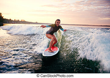 Female surfboarder - Young woman surfboarding at summer...