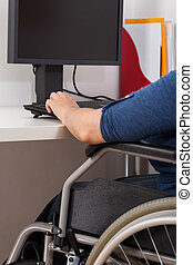 Disabled woman working next to computer, vertical