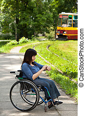 Girl on wheelchair waiting for tram - Girl on a wheelchair...