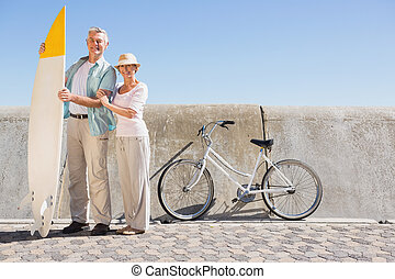 Happy senior couple posing with surfboard on a sunny day