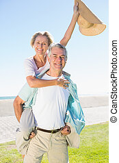 Happy senior man giving his partner a piggy back on a sunny...