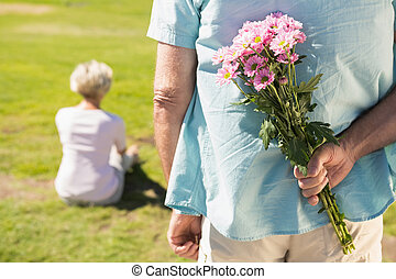 Senior man hiding flowers behind his back on a sunny day