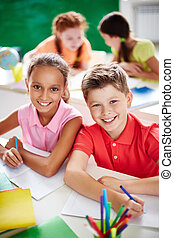 Happy friends - Two schoolkids looking at camera while...