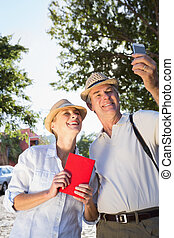 Happy senior couple looking at smartphone on a sunny day