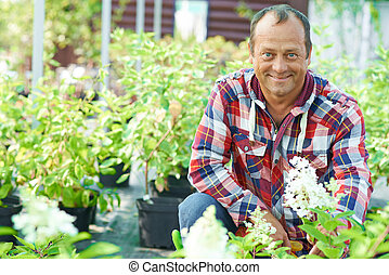 Male farmer - Happy male gardener looking at camera among...