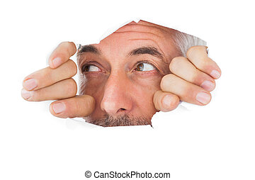 Man looking through torn paper on white background