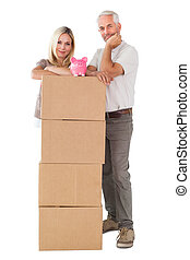 Happy couple leaning on pile of moving boxes with piggy bank...