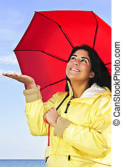 Beautiful young woman in raincoat with umbrella checking for...
