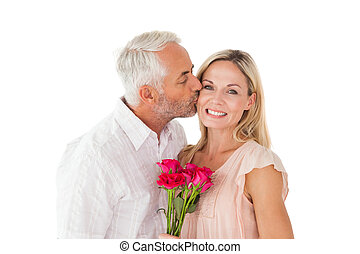Affectionate man kissing his wife on the cheek with roses on...