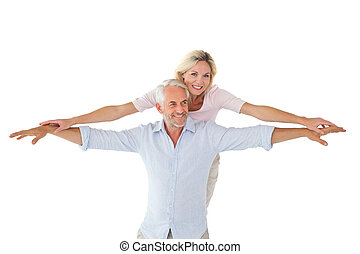 Smiling couple posing with arms out on white background