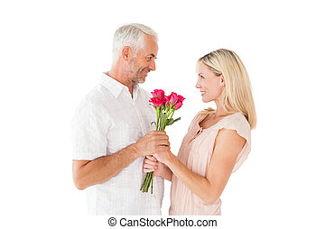 Affectionate man offering his partner roses on white...