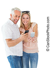Happy couple looking at their smartphones on white...