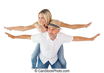 Happy man giving his partner a piggy back on white...