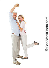 Smiling couple cheering at the camera on white background