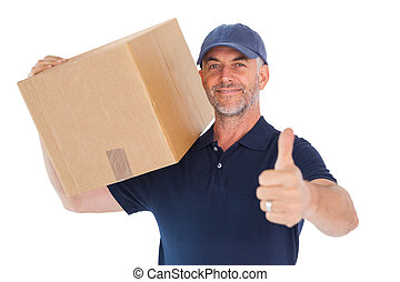 Happy delivery man holding cardboard box showing thumbs up...
