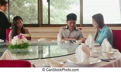 People eating at chinese restaurant, man, women, server...