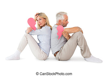 Unhappy couple sitting holding two halves of broken heart on...