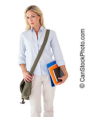 Blonde mature student carrying bag and books on white...