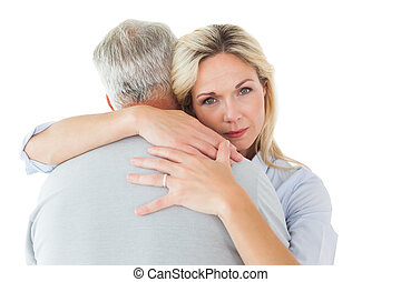 Unhappy blonde hugging her husband on white background