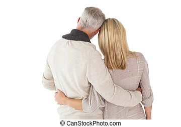 Happy couple standing with arms around on white background