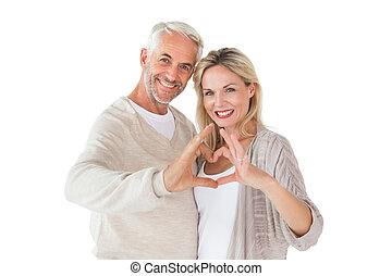 Happy couple forming heart shape with hands