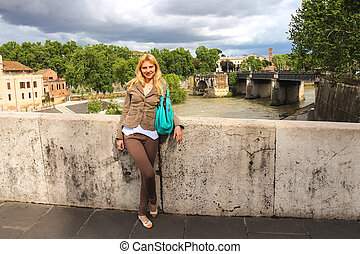 Attractive girl on the bridge across the Tiber in Rome,...