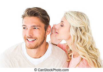 Attractive blonde whispering secret to boyfriend on white...