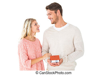 Attractive couple holding miniature house model on white...